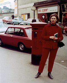 A woman standing on the pavement in a red suit color-matched to a postbox and a car, Manchester, England, United Kingdom, 1971, photograph by Martin Parr.