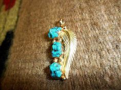 Stunning Navajo crafted 14k yellow gold three stone turquoise feather pendant.     www.EagleDancerGallery.com