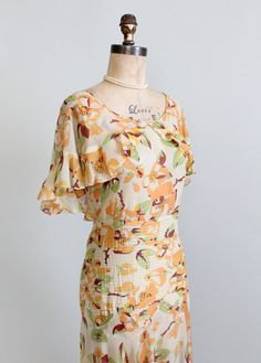 Vintage 1930s Floral Chiffon Summer Party Dress    -A breathtaking 1930s summer dress!  Lightweight, sheer chiffon with a sublime floral print in brown, green, and orange.  A fluttery capelet neckline.  Pin-tucking around the hips.  The bias cut skirt has a beautiful drape.  Side snaps.  So perfect for a late summer lawn party!