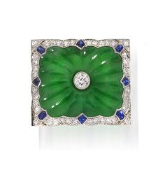 A jadeite jade, diamond and sapphire brooch  of rectangular outline, centering an old European-cut diamond within a carved radiating jade panel bordered by single-cut diamonds and fancy-shaped sapphires; mounted in platinum; width: 1in.