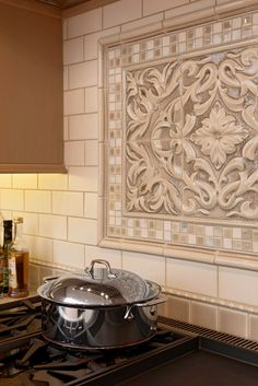 Encore Ceramics | This backsplash features the Grace plaque in Truffle crackle, framed with 1x1 mosaic in our Calacatta 904 blend, Positano molding glazed in Truffle crackle, and 3x6 field tile glazed in Brie gloss.  The bottom is finished with Peace liner and 3x3 field tile in Truffle crackle | Design by Davida's Kitchen & Tiles in Gaithersburg, MD