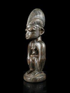 """33 Figur, """"ibeji"""" Yoruba, Nigeria H 28,5 cm.   Provenienz: Schweizer Privatsammlung, Zürich.  Über Zwillinge wurde schon immer gerätselt: Vergöttert oder verteufelt, in Legenden und Mythen, ja sogar in der Astrologie finden wir die Paare als Ausdruck der Faszination, die von ihnen ausgeht. So auch bei den Yoruba im Südwesten Nigerias, welche nachweislich die weltweit höchste Zwillingsgeburtenrate für sich beanspruchen können."""