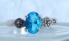 This ring is made of 925 Sterling Silver.  It has a prong set 7x5 mm oval cut blue cz.  It has a marcasite on each side of the shank.  This ring is size 7.