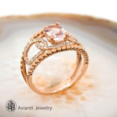 """This lovely Morganite engagement ring not only has a single halo of diamonds also some Oval Halo of diamonds going horizontally down on each side of the stone.  It also has ball design on both sides of the band. This ring is from our """"Blushing Rose"""" collection 