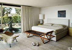 The master suite's custom-made bed by Prestigio is upholstered in Holly Hunt fabric. Hermès folding chaise; Hans Wegner lounge chair.
