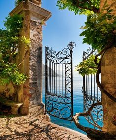 Ornate iron gate set into ancient wall opening onto the water. Lake Como, Italy.