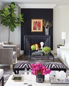 In designer Sloan Mauran's living room, a vintage painting on a bold back wall above the fireplace creates a focal point. | Photographer: Virginia Macdonald