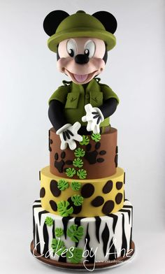 safari cake, mickey cake, four tier cake, covered with white and black, green brown and yellow fondant Cake Pops Mickey Mouse, Mickey Mouse Cake Decorations, Bolo Mickey Baby, Festa Mickey Baby, Mickey Mouse Birthday Cake, Mickey Mouse Baby Shower, Mickey Cakes, Safari Cakes, Safari Theme Party