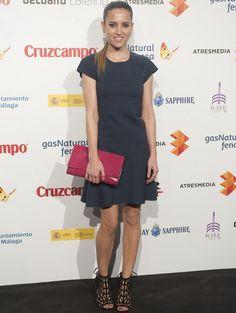 Ana Fernández combinó un minivestido lady en gris con sandalias jaula negras y una cartera XL en rosa fucsia.