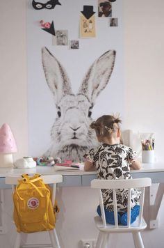 beautiful childrens space. Cute little double desk in pastel colours with two white chairs. The big bunny print adds a cute vibe to the simple design