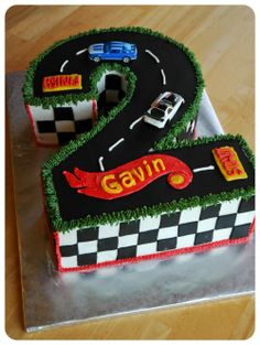Hot Wheels Birthday - 11x15 yellow cake with strawberry SMBC cut down to a #2. The cars are toys, all the black is fondant, and everything else is buttercream. We also had 2 dozen coordinating cupcakes, one dozen white and one dozen chocolate, iced in vanilla buttercream and topped with either a fondant wheel or a toy car.