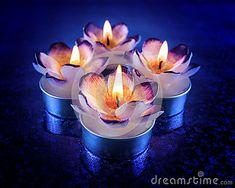 Flower shaped candles burning on blue reflective surface.