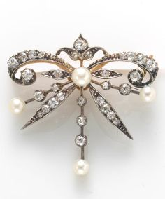 An antique diamond and cultured pearl brooch, circa 1880 featuring four cultured pearls measuring approximately 4.4 to 3.8mm; with original box; estimated total diamond weight: 1.00 carat; mounted in silver-topped ten karat gold; dimensions: 1 3/8 x 1 3/8in.