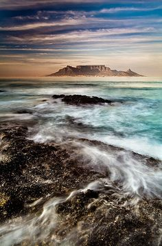 Table Mountain, South Africa.  Table Mountain is a flat-topped mountain forming a prominent landmark overlooking the city of Cape Town in South Africa, and is featured in the Flag of Cape Town and other local government insignia. (V)