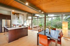 Ultra modern kitchen using traditional materials: light wood sloped ceiling, floor to ceiling glass exterior surface, large island in red wood with marble countertop, and natural hardwood flooring throughout.