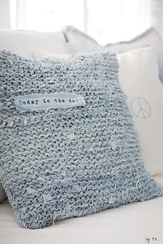Looks like she crocheted thin denim strips into a square, then sewed them to a block of denim to make a throw pillow.  So cute!