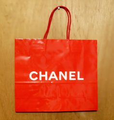Vintage 1990s Chanel Perfume Promotional Glossy Red Paper Shopping Bag Designer Fragrance Collectible. This was a promotional shopping bag given to a customer when they purchased a Chanel perfume in the 1990s. There was only a limited amount of these bags and not many survived. This one was saved by a long time perfume collector who worked at a high end department store in the 1980s to early 2000s and I was fortunate to acquire several more designer perfume promotional bags. This bag is…