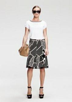T-shirt bianca con bordino bianco e nero che richiama la gonna svasata optical con patchwork di fantasie black&white. Bag neutra e occhialoni da diva