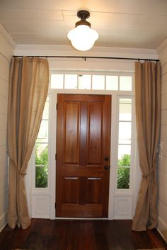 curtains in front of the front door windows.