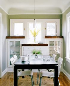 small dining room built in cabinets glass fronts modern table white chairs windows base board trim interior design home furnishings