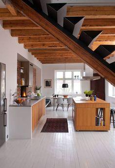 EKSPONERTE DRAGERE: Flere rom ble slått sammen for å danne ett stort allrom. Takbjelkene er blottet for å gi økt takhøyde som passer bedre til det nye rommets proporsjoner. Kjøkkenet er egendesignet og produsert av arkitektens far, Stein Haanshuus, på hans verksted på Røros.