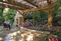 Beautiful pergola, stone retaining wall, plantings and fireplace.
