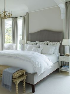 Elegant bedroom features a gray velvet camelback bed flanked by cream and black bone inlay nightstands topped with white Greek key column lamps alongside windows dressed in gray drapes.