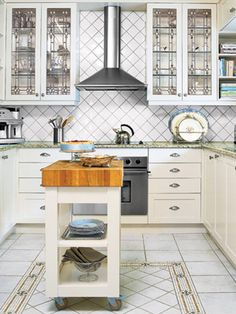 Pattern plays its many-faceted part in an all-white kitchen. A mosaic border frames porcelain floor tiles, and echoes the designs of the leaded-glass cabinetry and the backsplash. RELATED: 10 Ways to Decorate With White   - CountryLiving.com