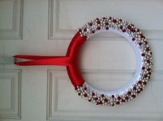 DIY Christmas wreath. Wrap foam wreath with ribbon then hot glue a ton of beads on it.