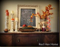 Fall mantle decor. I like the candle sticks, one with the pumpkin on top, and the frame