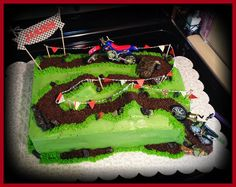 A quarter sheet red velvet cake decorated with cookie crumbs, green frosting, and candy rocks to create a dirt bike racing track complete wi...