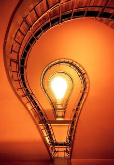 What exactly are you looking at? A glowing lightbulb? Not quite. It's actually a staircase in the inner city of Prague, taken from below and looking up by photographer Dennis Fischer. Love the beautiful saturated color and the incredibly cool perspective. Dennis Fischer on Flickr