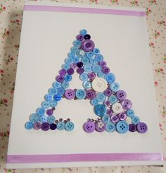 """Button and rhinestone initial, in blue and lilac, on a 10"""" x 8"""" box canvas. - The Supermums Craft Fair"""