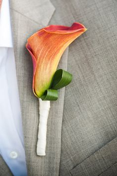 Groom, groomsmen, family members and ring bearer will wear orange calla lily boutonnieres wrapped in ribbon with the stem showing.