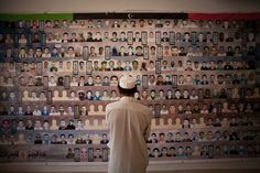 July 9, 2012. A Libyan man looks at a banner with photos of men who were killed during the revolution in Zintan, western Libya.
