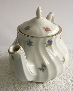 Beautiful vintage teapot made by Sadler in England.  The teapot stands 7.5 tall with floral details.  It is in good vintage condition, no