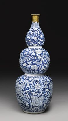 A MASSIVE BLUE AND WHITE TRIPLE-GOURD VASE QING DYNASTY, KANGXI PERIOD the two lower bulbs painted on a bright blue ground with lively dragons striding amidst luxuriant floral meander bearing large peony, lotus and chrysanthemum blooms, the upper bulb painted with three shaped floral medallions below a band of upright acanthus leaves, the rim and upper section of the neck with gilt mount Height 36 1/2 in