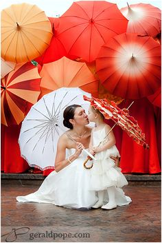 Classic Creations: Rain, Rain, Go Away. Red Parasols background. Bride and flower girl pose.