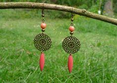 Boucles d'oreilles composées d'une estampe et d'une perle métallique bronze, d'une perle de verre et d'une navette émaillée corail. S'attachent par un crochet d&…