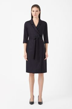 Crossing over at the front, this wool dress is based on the shape of a blazer with slim notched lapels. Fully lined in a silky fabric, it has neat half sleeves, hidden button fastening and a detachable tie-waist fastening.