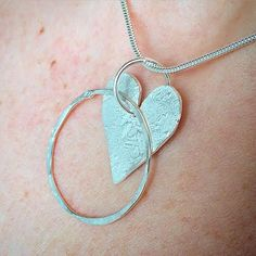 Simple yet stylish, this silver heart and hammered circle pendant was lovingly crafted in our studio.