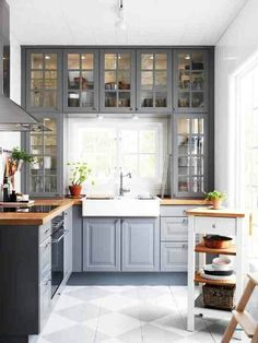glass doors, gray cabinets, butcher block counter, white backsplash