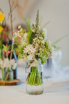 love the simplicity of the green and white, and the different textures and heights of the bouquet.  Also, jars would be excellent to hold bouquets during the reception