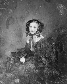 This is an old, severely scratched up daguerreotype of a beautiful, melancholy, young lady. This image dates to about the early 1850's
