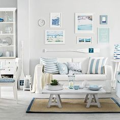 Bring an element of the coast to your own home with this white living room. The blue pictures and paintings combined with the striped cushions, bowls and seat cushions create an inspirational coastal look.