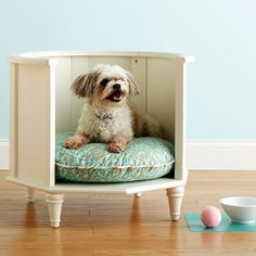 """Pamper your pooch by building a bed made from an unused side table. Remove the top and doors, then cut away any support pieces. After sanding rough edges, apply a fresh coat of paint that will complement your space. Finish by placing a fluffy dog pillow inside."""