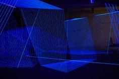 Jeongmoon Choi: installation at Opernwerkstätten, Berlin, with threads illuminated by black light