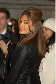 For this look, Eva Mendes has very long, thick hair. Her hair falls long on her back and is build up high on top as the sides have been brushed and gathered towards the back, then clipped in place. At the front, long bangs are styled at both sides.Eva's haircut is long.The hair is coloured a dark brown with auburn highlights.