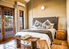 Wolfkop Nature Reserve Mountain Cottages het pragtige kamers met 'n tikkie Suid-Afrikaanse flair, soos dié een met 'n protea-motief op die kussings.