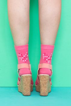 Update a pair of plain, colorful socks with paint to create these faux cross stitch heart socks to wear with tennis shoes, sandals or heels for Valentine's Day or just because!